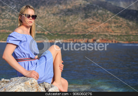 Summer portrait of beautiful girl in sunglasses who is sitting near the sea and mountains stock photo, Summer portrait of beautiful girl in sunglasses who is sitting near the sea and mountains. by Alfira Poyarkova