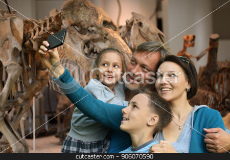 Portrait of happy family taking selfie with smartphone stock photo, Happy family taking selfie with smartphone at Natural History Museum by Ruslan Huzau