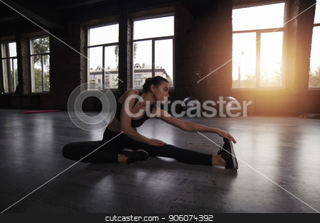 Athletic girl does stretching exercises at the gym stock photo, Determined athletic girl does stretching exercises at the gym by Federico Caputo