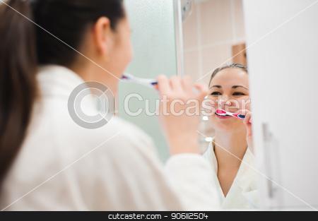 Portrait of young beautiful woman brushing her teeth stock photo, Portrait of young beautiful woman brushing her teeth with toothbrush by Oleksandr Nagaiets