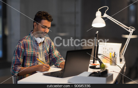 creative man with laptop working at night office stock photo, deadline, technology and people concept - creative man with laptop computer working at night office and writing to notebook by Syda Productions