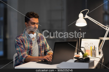 creative man with laptop working at night office stock photo, deadline, technology and people concept - creative man with laptop computer working at night office by Syda Productions