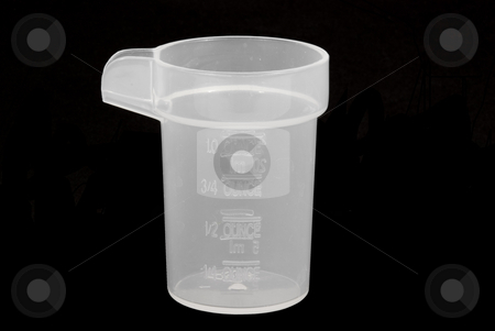 Small measuring cup stock photo, Small measuring cup on black background by John Teeter