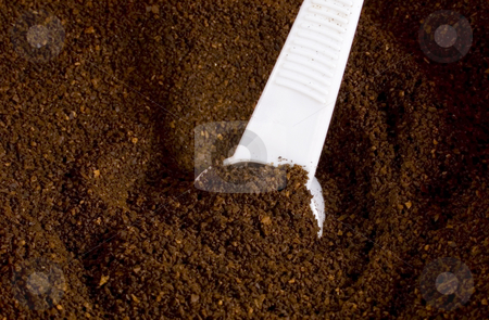 Coffee grounds with scoop stock photo, Coffee ground with white scoop by John Teeter