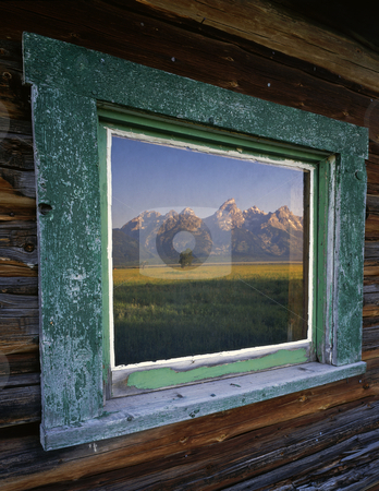 Teton Window stock photo, The Teton Mountain Range reflecting in the window of a ranch house, located in Grand Teton National Park, Wyoming. by Mike Norton