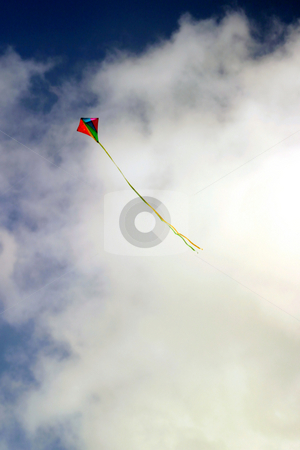 Kite stock photo, Colorful kite in flight against white clouds by Henrik Lehnerer