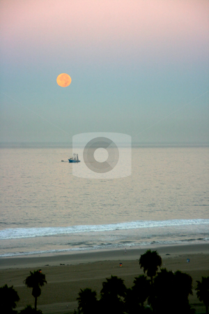 Moon setting in the morning over a fishing boat stock photo, The moon is setting behind an early morning fishing boat going out for the day by Mitch Aunger