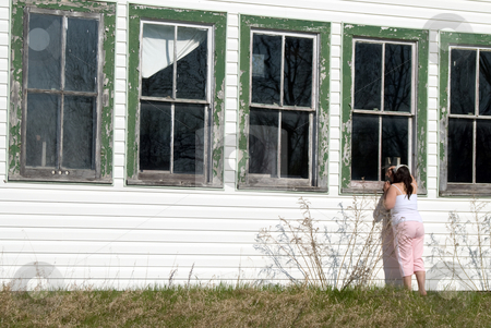 Spying stock photo, A young girl looking in a window of an old abandoned schoolhouse by Richard Nelson