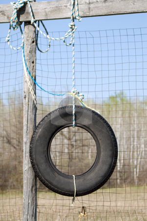 Tire Swing stock photo, An old tire swinghanging from a beam by Richard Nelson