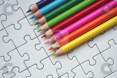 Pencils on jigsaw background stock photo, Jigsaw puzzle with a rainbow colored row of pencils by Gautier Willaume