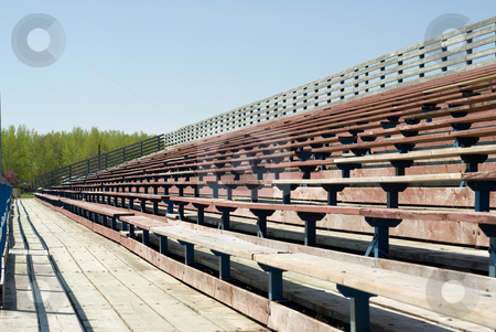 Empty Bleachers stock photo, Rows of empty wooden bleachers outside on a sunny day by Richard Nelson