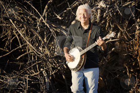 Banjo Player stock photo, Banjo player with his instrument in front of a pile of sticks by Scott Griessel