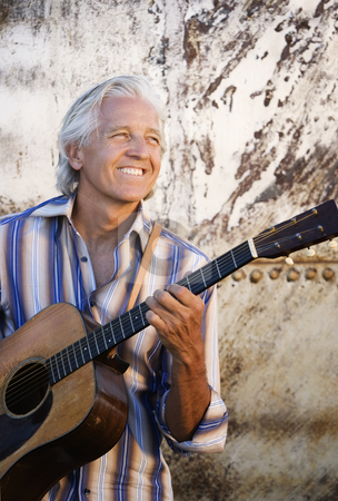 Guitar Player stock photo, Guitar player with his instrument in golden light by Scott Griessel