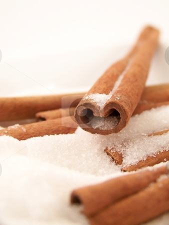 Cinnamon Sticks and Sugar stock photo, Vertical image of a single heart-shaped cinnamon stick in white granulated sugar, with others visible. by Jill Oliver