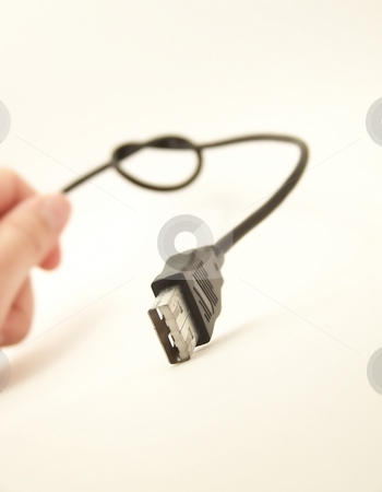 USB Cable and Hand 3 stock photo, Image of a knotted USB cable, with hand entering frame in background. by Jill Oliver