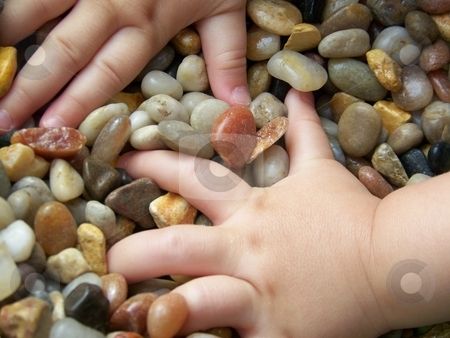 Image of Child's Hands in Pebbles stock photo, Image of a young child's hands reaching into a pile of multicoloured pebbles. by Jill Oliver