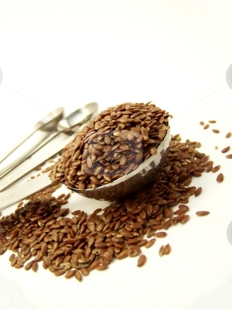 Flax Seed Overflowing Measuring Spoon, Angle stock photo, Angled image of whole flax seed overflowing a measuring spoon, with other measuring spoons in the background. by Jill Oliver