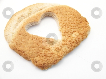 Hearty Wheat Bread, Angled stock photo, Image of a slice of wheat bread with a heart cut out, placede at an angle.  White background, horizontal orientation. by Jill Oliver