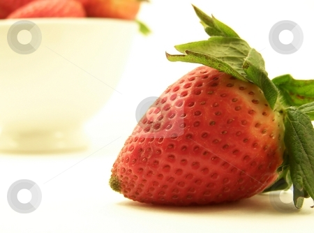 Strawberries, Horizontal stock photo, Close up image of a large red strawberry, with other strawberries in a bowl in the background.  White background and horizontal orientation. by Jill Oliver