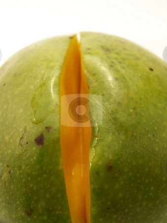 Sliced Mango stock photo, Close up image of a bright green mango with a small slice removed. by Jill Oliver