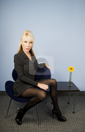 Beautiful Businesswoman stock photo, Beautiful businesswoman sitting in front of a blue wall by Scott Griessel