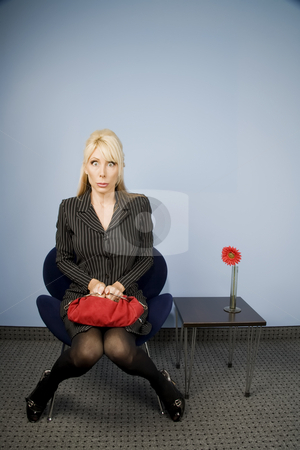 Apprehensive woman sitting waiting in an office chair  stock photo, Beautiful blonde woman waiting with a worried look on her face by Scott Griessel