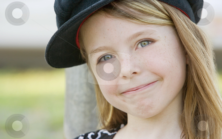 Cute Young Girl stock photo, Close up of a young girl wearing a cap by Scott Griessel