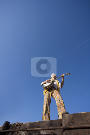 Banjo Player stock photo, Banjo Player with groovy clothes against a wide sky by Scott Griessel
