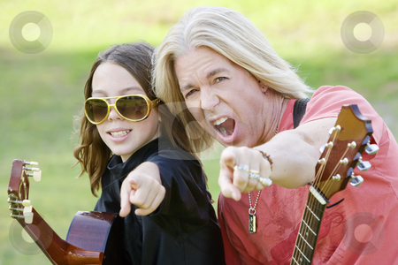 Rock and Roll Dad and Son stock photo, Father and son with guitars point at the camera by Scott Griessel