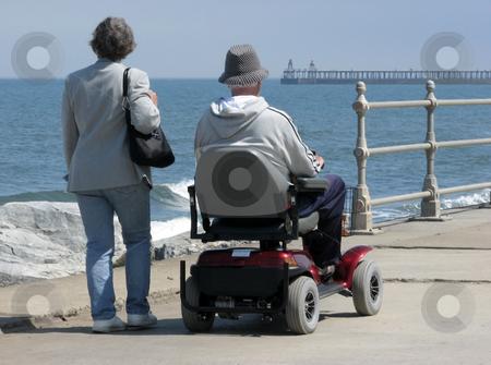 Motorized wheelchair user stock photo, Elderly man riding motorized wheelchair with woman on seaside promenade. by Ronald Hudson