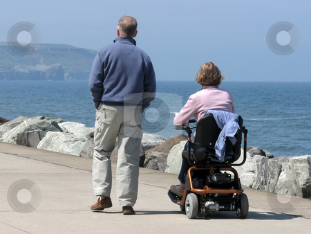 Couple on promenade stock photo, Couple strolling on seaside promenade. Woman riding motorized wheelchair. by Ronald Hudson
