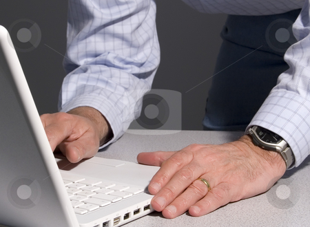 Man using laptop stock photo, Man using computer laptop while leaning over desk. by Ronald Hudson