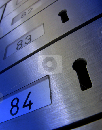 Mail boxes stock photo, Distorted view of letter boxes with keyholes. Overlaid with blue for effect. by Ronald Hudson