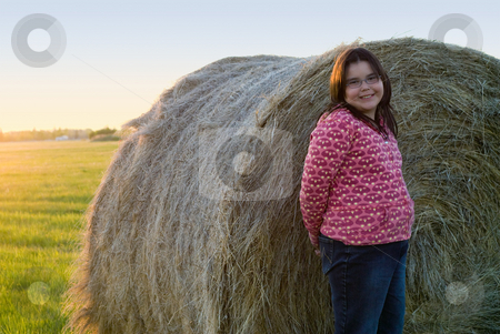 Farm Girl Portrait stock photo, A young girl posing in front of a large hay bale by Richard Nelson