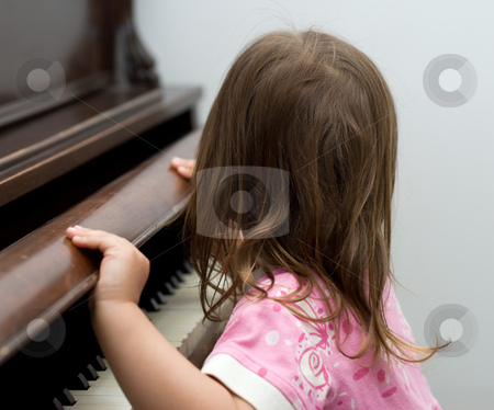 Pianist stock photo, Girl opening the keyboard cover on a piano by Richard Nelson