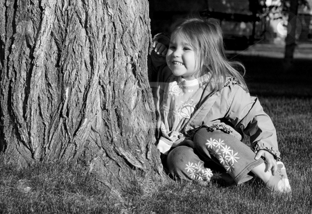 Taking A Break stock photo, Little girl sitting by tree smiling in black and white by Richard Nelson