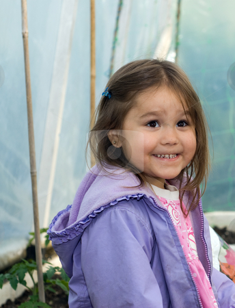 Girl In Greenhouse stock photo, A young girl smiling inside a greenhouse by Richard Nelson