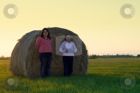 Farm Girls stock photo, Two young girls standing in front of a hay bale by Richard Nelson