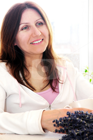 Mature woman relaxing stock photo, Smiling mature woman relaxing at home holding a cup by Elena Elisseeva