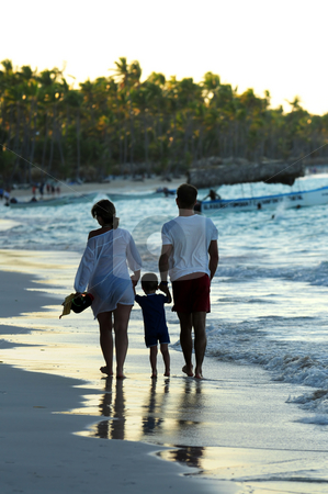 Family walking on a beach stock photo, Family taking a walk on a sandy beach of tropical resort by Elena Elisseeva