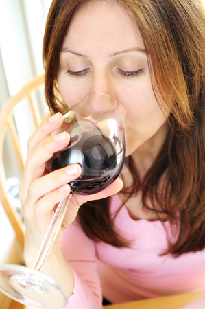 Mature woman with a glass of red wine stock photo, Mature woman holding a glass of red wine by Elena Elisseeva