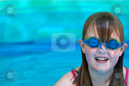 Girl wearing goggles stock photo, A young girl with swimming goggles in an inflatable pool with room on right for type by Vince Clements