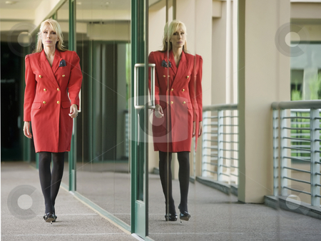 Businesswoman Reflected stock photo, Businesswoman in a red suit reflected in building glass by Scott Griessel