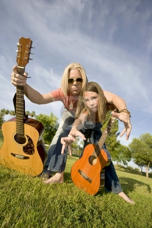 Rock and Roll Dad and Son stock photo, Father and son with guitars grab at the camera by Scott Griessel