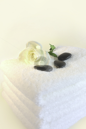 White towels stock photo, Luxurious spa towels with white rose and black pebbles by ImageZebra .