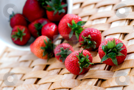 Fresh strawberrys on a woven platter stock photo, Fresh strawberrys on a woven platter spilling from a white bowl by Vince Clements