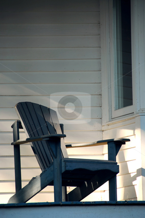 Porch chair stock photo, Wooden chair on a sunlit porch of a house by Elena Elisseeva