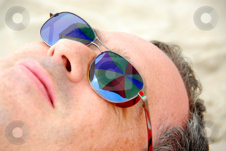 Man beach relax stock photo, Man relaxing on a beach, focus on umbrella reflections in man's sunglasses by Elena Elisseeva