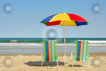 Beach chairs and umbrella stock photo, Beach chairs and umbrella on the ocean shore with surf in the background, horisontal by Elena Elisseeva