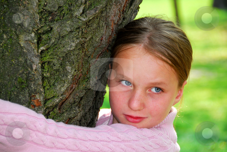 Girl and big tree stock photo, Young girl standing near ancient big tree, closeup by Elena Elisseeva